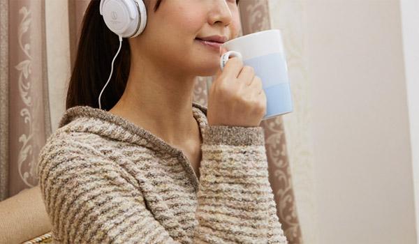 音楽を聴きながら飲み物を飲む女性